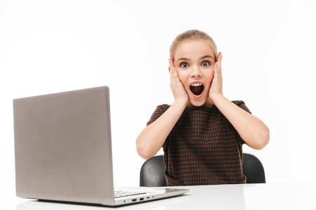Portrait of shocked school girl rejoicing and using silver laptop while sitting at desk in class isolated over white background