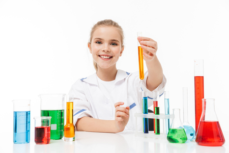 Portrait of blond little girl in white laboratory coat making chemical experiments with multicolored liquid in test tubes isolated over white background