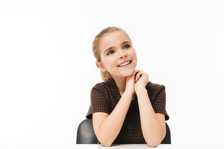 Portrait of pretty school girl sitting at desk on lesson while studying subjects at school isolated over white background