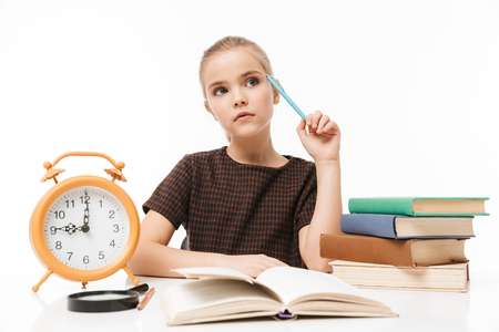Portrait of happy school girl with big alarm clock on desk studying and reading books in class isolated over white background