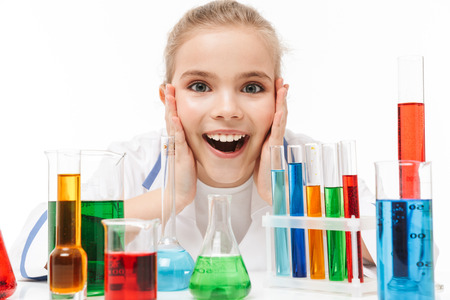 Image of european school girl in white laboratory coat making chemical experiments with multicolored liquid in test tubes isolated over white background