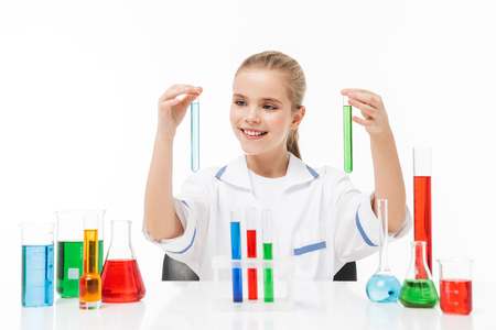 Portrait of positive little girl in white laboratory coat making chemical experiments with multicolored liquid in test tubes isolated over white background
