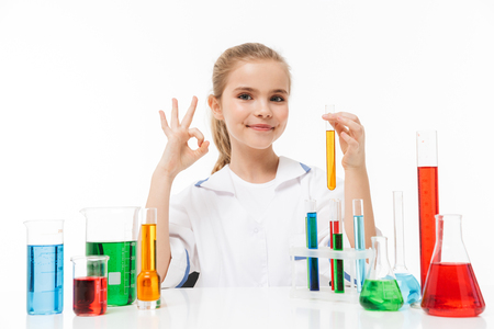 Portrait of cheerful little girl in white laboratory coat making chemical experiments with multicolored liquid in test tubes isolated over white background
