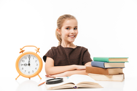 Portrait of lovely school girl with big alarm clock on desk studying and reading books in class isolated over white background