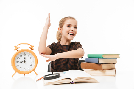 Portrait of positive school girl with big alarm clock on desk studying and reading books in class isolated over white background