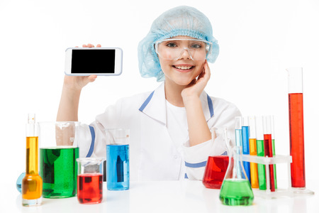 Photo of positive little girl in white laboratory coat using smartphone during chemical experiments with multicolored liquid in test tubes isolated over white background