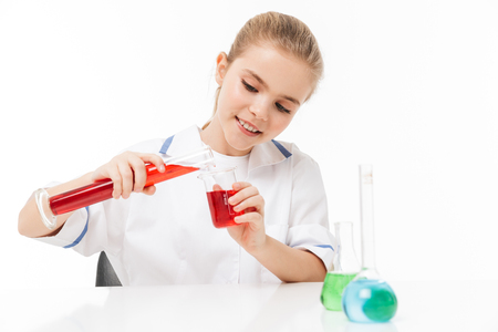 Portrait of smart little girl in white laboratory coat making chemical experiments with multicolored liquid in test tubes isolated over white background Stock Photo