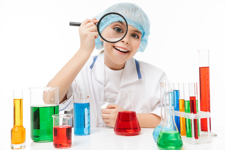 Portrait of microbiologist little girl in white laboratory coat holding magnifying glass during chemical experiments isolated over white background Stock Photo
