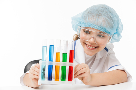 Portrait of amusing little girl in white laboratory coat making chemical experiments with multicolored liquid in test tubes isolated over white background