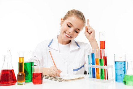 Image of beautiful school girl in white laboratory coat making chemical experiments with multicolored liquid in test tubes isolated over white background