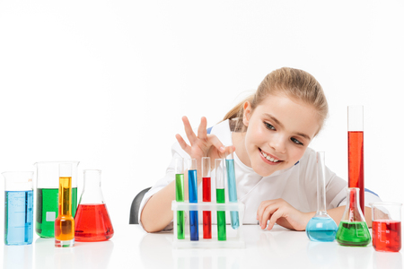 Portrait of happy little girl in white laboratory coat making chemical experiments with multicolored liquid in test tubes isolated over white background