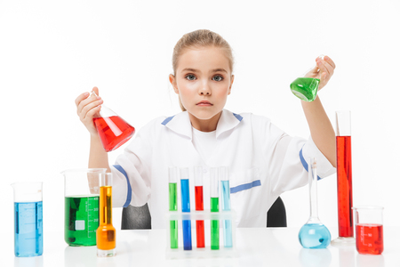 Portrait of little pupil girl in white laboratory coat making chemical experiments with multicolored liquid in test tubes isolated over white background