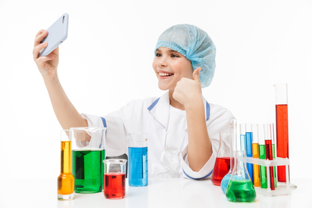 Photo of cute little girl in white laboratory coat using smartphone during chemical experiments with multicolored liquid in test tubes isolated over white background Stock Photo