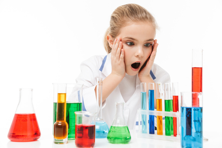 Image of excited school girl in white laboratory coat making chemical experiments with multicolored liquid in test tubes isolated over white background Stock Photo
