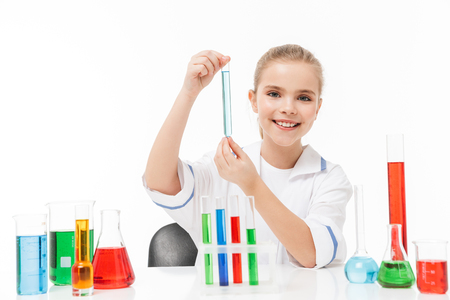 Portrait of caucasian little girl in white laboratory coat making chemical experiments with multicolored liquid in test tubes isolated over white background Stock Photo