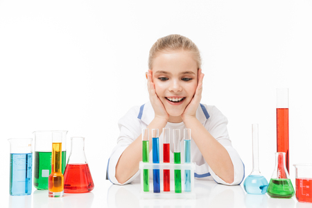 Portrait of beautiful little girl in white laboratory coat making chemical experiments with multicolored liquid in test tubes isolated over white background Stock Photo