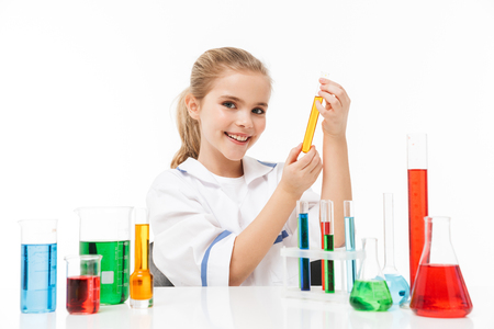 Portrait of adorable little girl in white laboratory coat making chemical experiments with multicolored liquid in test tubes isolated over white background Stock Photo