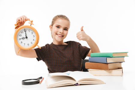 Portrait of beautiful school girl holding big alarm clock while studying and reading books in class isolated over white background