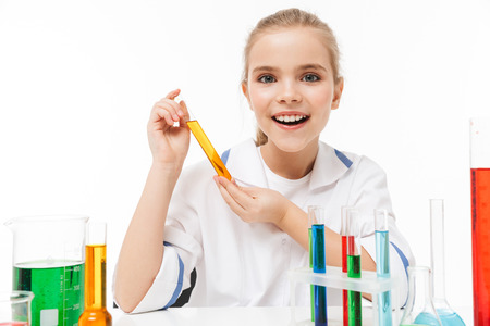 Portrait of lovely little girl in white laboratory coat making chemical experiments with multicolored liquid in test tubes isolated over white background
