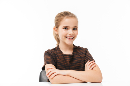 Portrait of european school girl sitting at desk on lesson while studying subjects at school isolated over white background