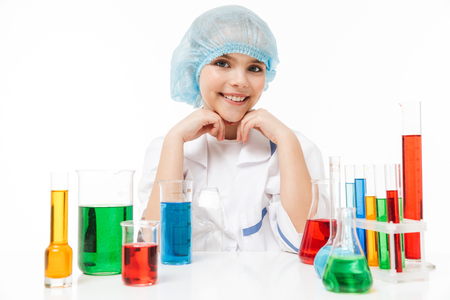 Portrait of cute little girl in white laboratory coat making chemical experiments with multicolored liquid in test tubes isolated over white background