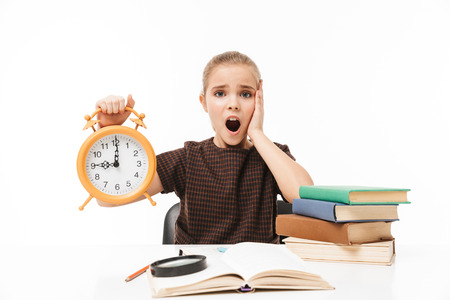 Portrait of young school girl holding big alarm clock while studying and reading books in class isolated over white background
