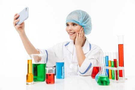 Photo of happy little girl in white laboratory coat using smartphone during chemical experiments with multicolored liquid in test tubes isolated over white background