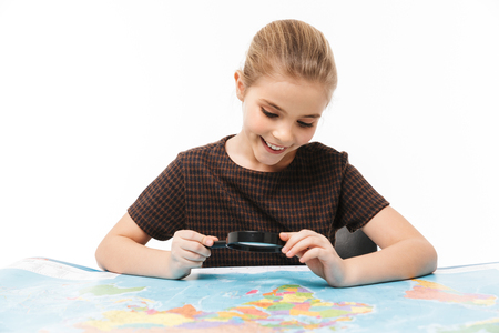 Portrait of beautiful school girl looking at world map through magnifying glass while studying geography in school isolated over white background Reklamní fotografie