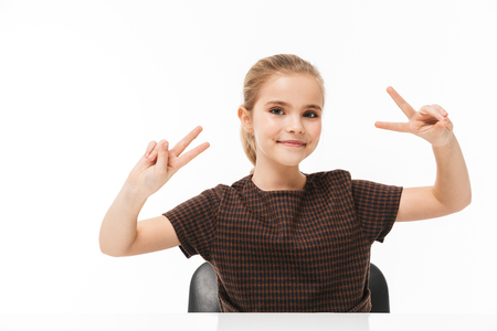 Portrait of happy school girl smiling and showing peace sign while sitting at desk in class isolated over white background Reklamní fotografie