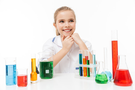 Portrait of cheery little girl in white laboratory coat making chemical experiments with multicolored liquid in test tubes isolated over white background Stock Photo