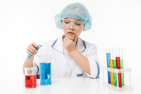 Portrait of concentrated little girl in white laboratory coat making chemical experiments with multicolored liquid in test tubes isolated over white background