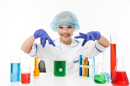 Portrait of little chemist girl in white laboratory coat making chemical experiments with multicolored liquid in test tubes isolated over white background Stock Photo