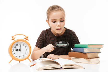 Portrait of caucasian school girl with big alarm clock on desk studying and reading books in class isolated over white background
