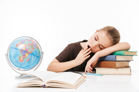 Portrait of sleepy school girl reading studying books and doing homework while sitting at desk in class isolated over white background