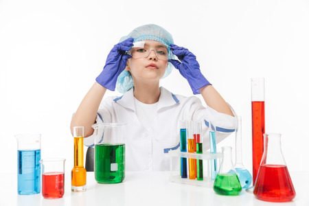 Portrait of serious little girl in white laboratory coat making chemical experiments with multicolored liquid in test tubes isolated over white background Stock Photo