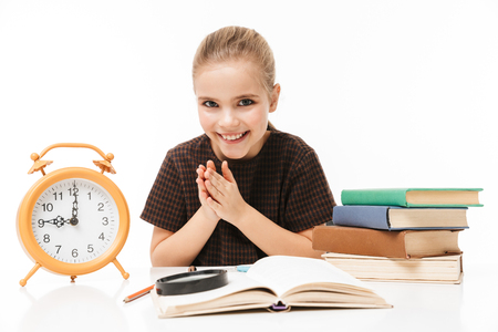 Portrait of european school girl with big alarm clock on desk studying and reading books in class isolated over white background