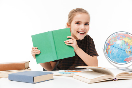 Portrait of young school girl reading studying books and doing homework while sitting at desk in class isolated over white background