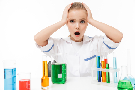 Portrait of excited little girl in white laboratory coat making chemical experiments with multicolored liquid in test tubes isolated over white background