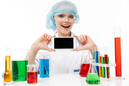 Photo of joyous little girl in white laboratory coat using smartphone during chemical experiments with multicolored liquid in test tubes isolated over white background