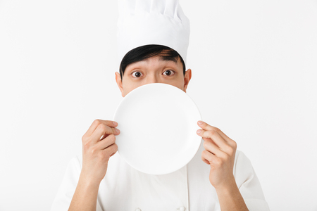 Image of asian pleased chief man in white cook uniform smiling at camera while holding a plate isolated over white background 写真素材