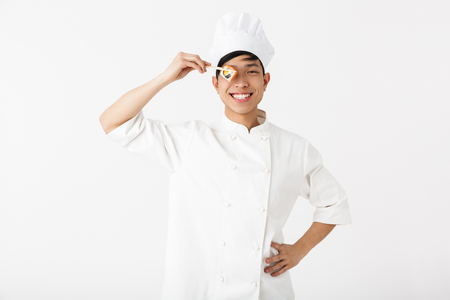Excited asian chef wearing uniform standing isolated over white background, preparing sushi