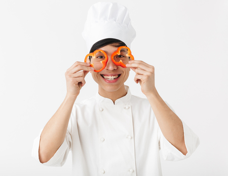 Excited asian chef wearing uniform standing isolated over white background, having fun, holding sliced capsicum Stockfoto