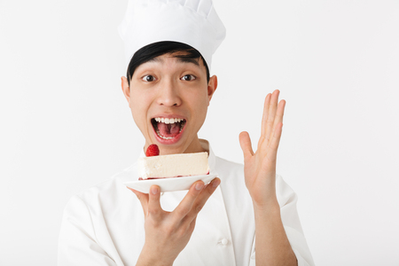 Image of cheery chinese chief man in white cook uniform smiling at camera while holding platter with tasty cheesecake isolated over white background Reklamní fotografie