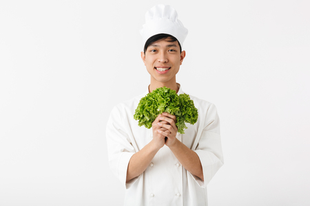 Image of asian optimistic chief man in white cook uniform smiling at camera while holding green lettuce salad isolated over white background Imagens