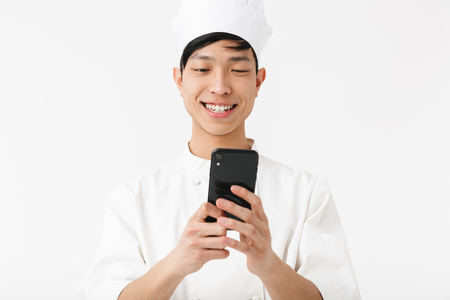 Image of cheerful chinese chief man in white cook uniform and chef's hat holding mobile phone isolated over white background