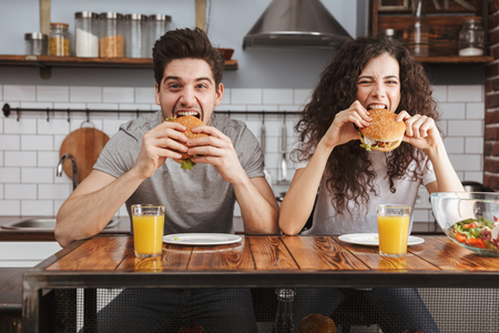 Cheerful happy couple eating burgers at the kitchen