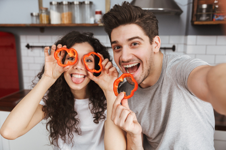 Cheerful couple at the kitchen, having fun, taking a selfie