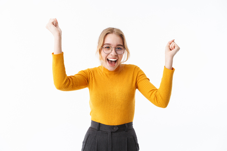 Attractive young blonde woman wearing sweater standing isolated over white background, celebrating success