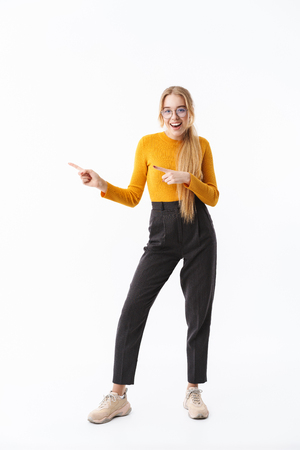 Full length of a smiling attractive young blonde woman wearing sweater standing isolated over white background, presenting copy space Reklamní fotografie