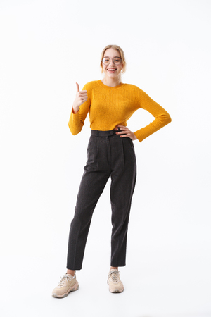 Full length of a smiling attractive young blonde woman wearing sweater standing isolated over white background, thumbs up